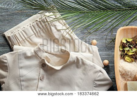Composition with spa uniform on wooden background
