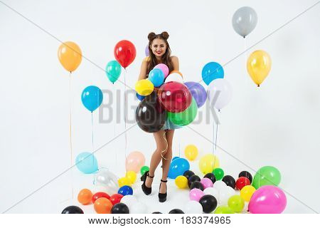 Pretty stylish girl with fashion hairstyle and on high heels posing with bunch of balloons