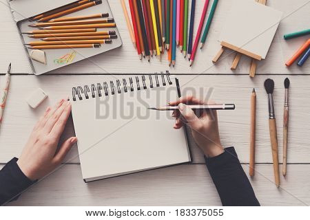 Draw in sketchbook. Creative artist workspace top view. Background of painting, art stationery