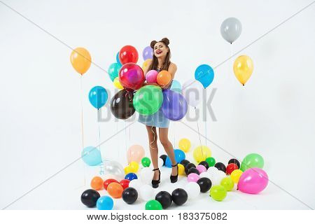 Happy woman in cool summer wear looks glad playing with helium ballons after bright party