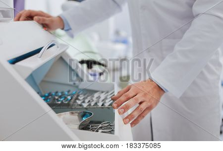 Look here. Special box standing in consulting room, doctor holding his hands on it while choosing instrument