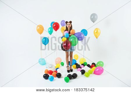 Adorable school girl in fancy clothing posing on prom holding colourful balloons wearing elegant dress