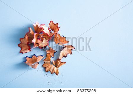 Pencil sharpening shavings on blue background. Art and education