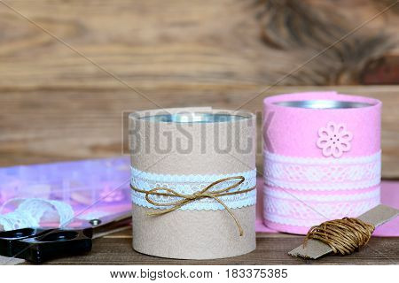 Recycled tin cans for storage. Easy and cheap idea for beautiful decorating old things. Recycled craft concept. Wooden background