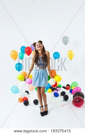 Young girl in trendy fashion look posing with small coloured balloons in illuminated white room
