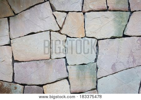 Multi-colored and multi-sized pale rocks wall grunge texture background.