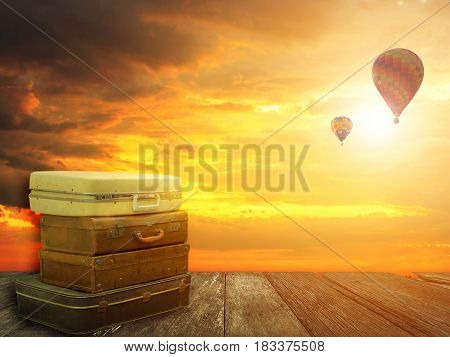 Stacked leather luggage on wood plank with hot air balloons in sunset sky background. Travel concept. Best journey with fantasy nature background.