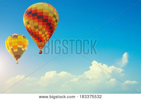 Two colorful hot air balloons up in the beautiful blue sky with cloud. Travel background concept with free space for text. Fresh nature and relax vacation.