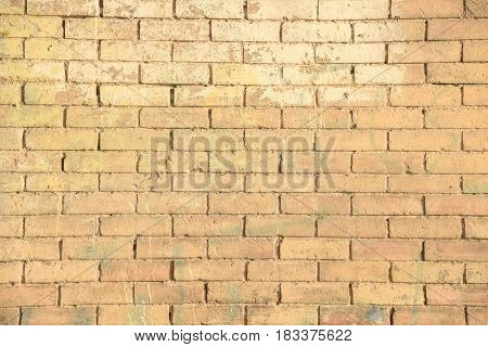 Abstract weathered brown-yellow grunge brick wall texture or old surface pattern for vintage room background and backdrop architectural element in urban concept