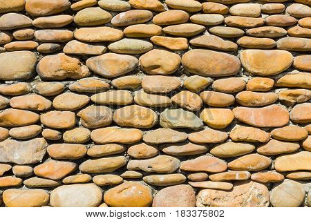 River pebbles round stone wall background in Thailand