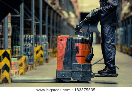 Worker loading pallet with pallet jack in modern warehouse.