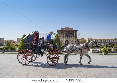 ISFAHAN IRAN - OCTOBER 22 2016 : Iranians sit on carriage during visit the Naghsh-e Jahan Square (Imam Sqaure) UNESCO World Heritage Sites in Isfahan (Esfahan) Iran.