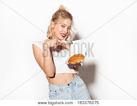 Young fit female in casual clothing looking at camera and pointing at burger on white background.