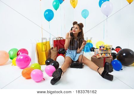 Bright birthday party. Nice fashion girl phone receiver in hands amazed and surprised looking away