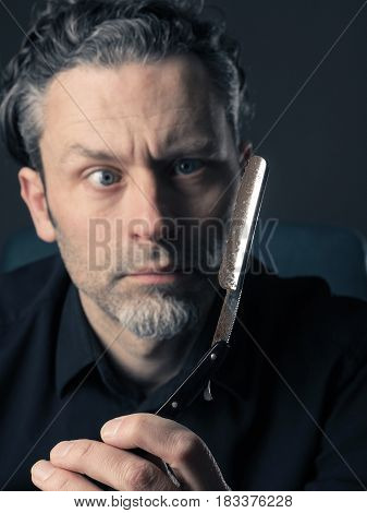 Handsome man with a rusty old shaving knife looking scary