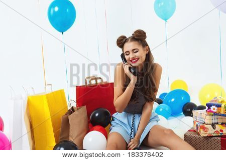 Shy and pretty girl sitting with birthday gifts receiving wishes on phone, looking down, blushing
