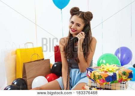Adorable girl with fancy hairstyle fielding calls and looking straight after big birthday party