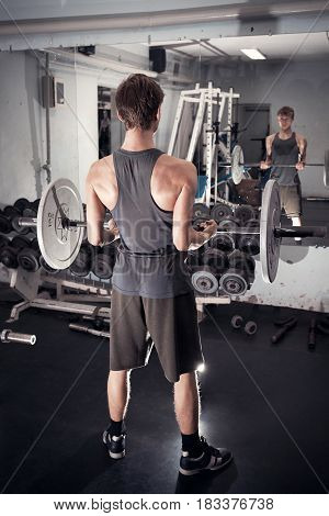 Exercise on the biceps with the barbell. A young athletic man performs. Standing with your back Retro effect