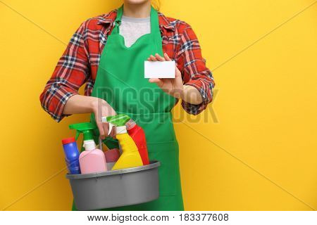 Young charwoman with business card and cleaning supplies on color background