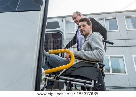 Low angle view of professional taxi driver assisting disabled man to board van outside building
