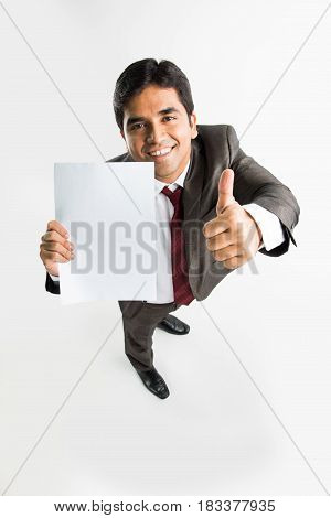 indian young businessman holding a blank white paper and showing success sign or thumbs up, a bird's eye view from top showing perspective view of man