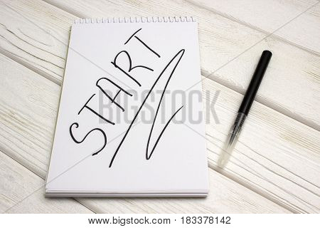 A notebook with an inscription is start and black marker on white wooden table