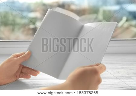 Human hands holding blank brochure near window