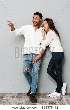 Full-length shot of smiling man standing with surprised woman pointing away isolated