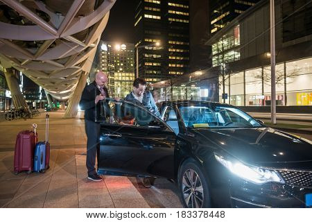 Male professional driver assisting passenger entering car on city street at night
