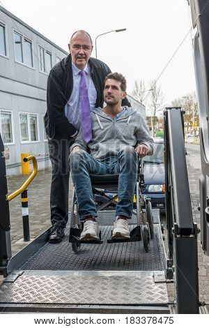 Taxi driver assisting man on wheelchair to board hydraulic lift van