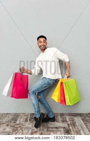 Picture of young smiling african man standing over grey wall and holding shopping bags. Looking at camera.