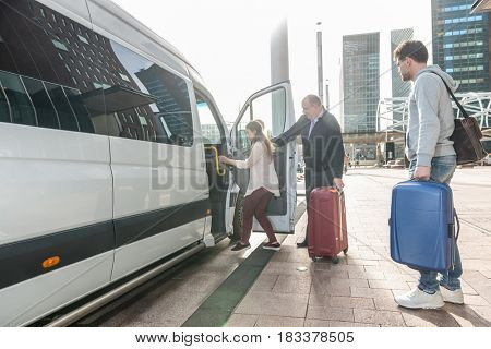Taxi driver with luggage assisting female passenger to board van at airport