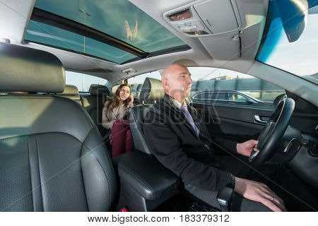 Professional driver riding taxi while female passenger talking on mobile phone