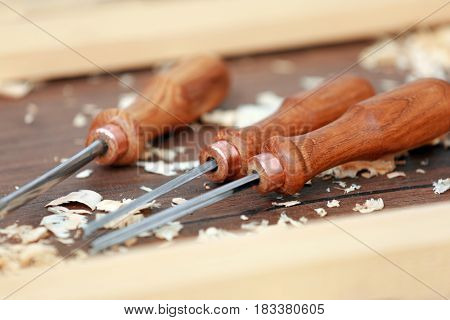 Set of chisels on wooden table in workshop