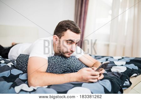 Young Cell Phone Addict Man Awake At Night In Bed Using Smartphone For Chatting, Flirting And Sendin
