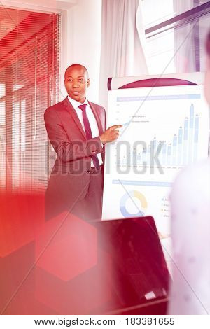 Young businessman explaining graph while giving presentation in office