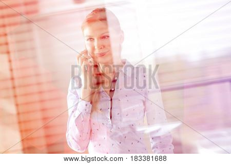 Smiling young businesswoman using mobile phone at office