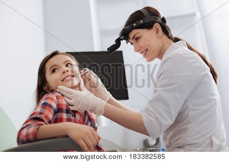 Everything is okay. Attractive otolaryngologist putting her hands on the face of a girl looking into ear while sitting in semi position