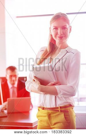Portrait of confident young businesswoman holding tablet PC with businessman in background at office