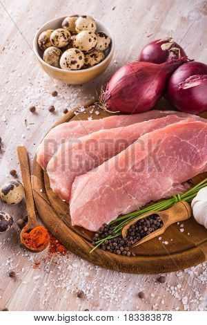 Several Slices Of Raw Pork Meat On Wooden Plate With Spices