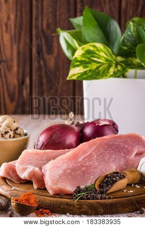 Three Slices Of Raw Pork Meat On Wooden Plate With Spices