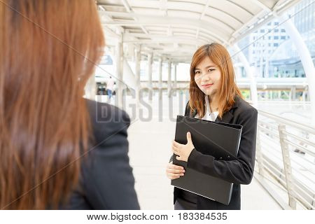 Young asian businesswoman holdind file and looking at colleague - business concept