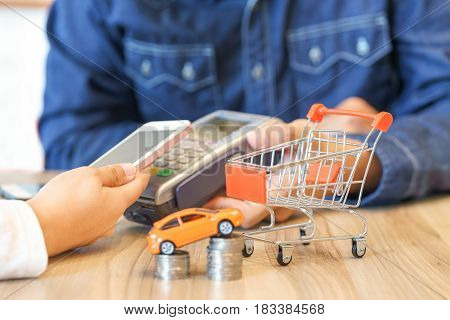 Woman paying for a new car via smartphone with red shopping cart car toy and coins concept