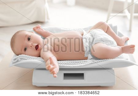 Cute little baby lying on scales at home