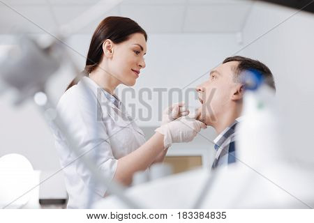 Throat exam. Smiling woman holding otolaryngologist instrument touching chin of her visitor while treating him