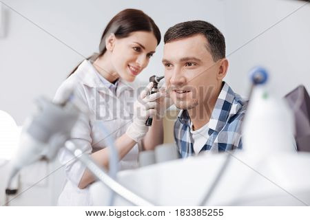 I cannot wait. Confident otolaryngologist holding medical instrument touching ear of her patient while looking at him