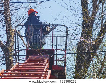 Worker with a chainsaw on the lift machine