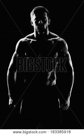 Vertical black and white silhouette of a shirtless athletic man with muscular strong body posing confidently on black background masculine brutal sportsman bodybuilder fitness athleticism concept.