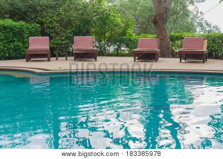 Relaxation Concept : Daybed beside swimming pool on concrete floor with blue green water and bush background.