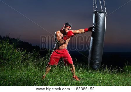 Shirtless muscular young male fighter hitting a punching bag training outdoors on sunset copyspace sportive sports sportsman lifestyle motivation powerful strong muscular abs torso body fitness toning.